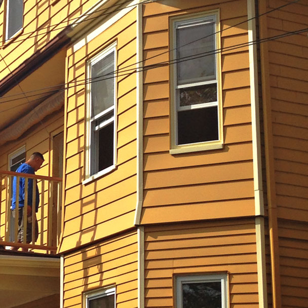 Workers painting the exterior of a house yellow in Wakefield, MA